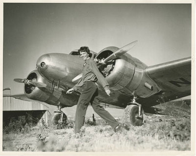 Amelia Earhart walking in front of her Lockheed Electra airplane, ca. 1930s