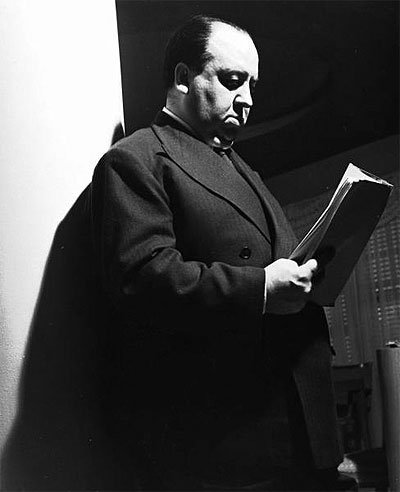 """Movie dir. Alfred Hitchcock dourly reading script for the movie """"Rebecca"""" as he stands against a pillar in his small apt. in the Wilshire Palms. Photo taken 1939 by Peter Stackpole"""