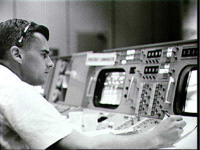 Astronaut Roger B. Chaffee is shown at the consoles in the Mission Control Center - Houston during the Gemini-Titan 3 flight.