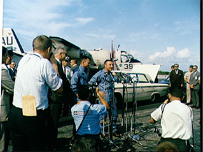 Astronauts John W. Young (left) and Viril I. Grissom stand before microphones at Cape Kennedy's skid strip during welcome back ceremonies for Gemini-3 crew.