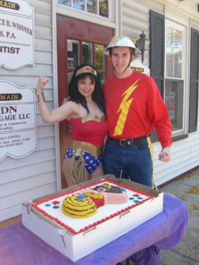 Amber as Wonder Woman and Andrew Moser as Jay Garrick/Flash pose with the cake created & donated by a Comic Fusion customer