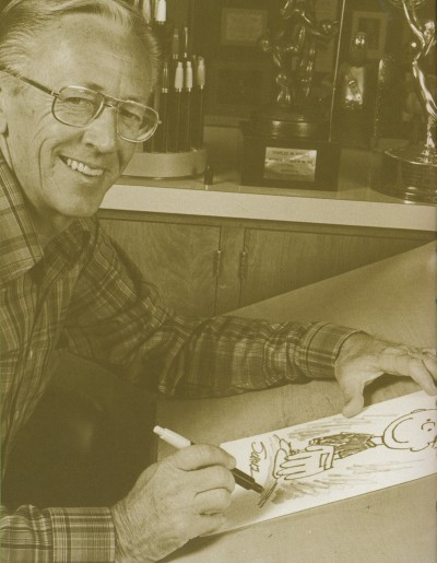 Charles Schulz in his later years with a drawing of Charlie Brown